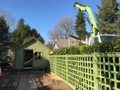 A shoring crane in place in the alley with a cross bar to pick the shed up straight and level